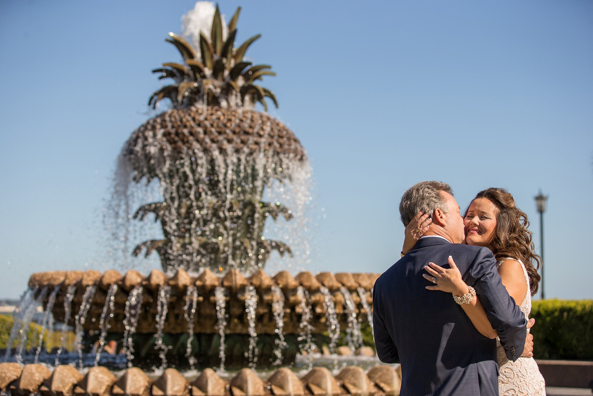 The couple is hugging near the Pineapple fountain