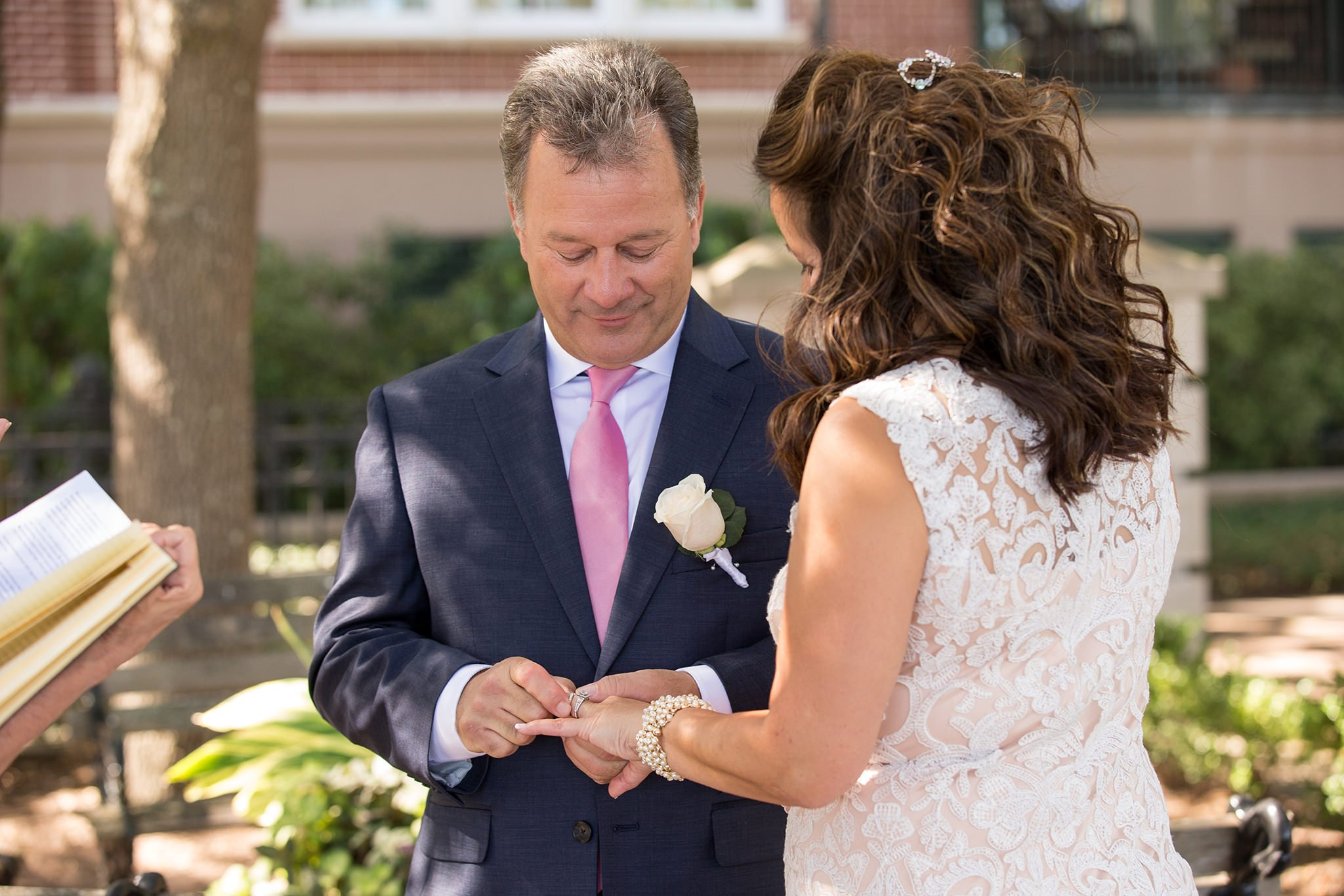 The groom is putting the ring on the bride's finger