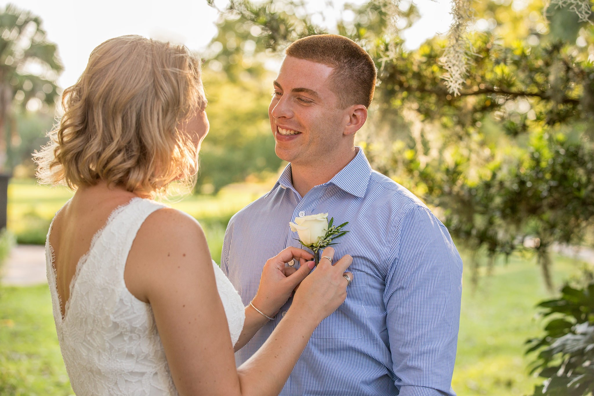 The bride is fixing the flower on the groom's shirt