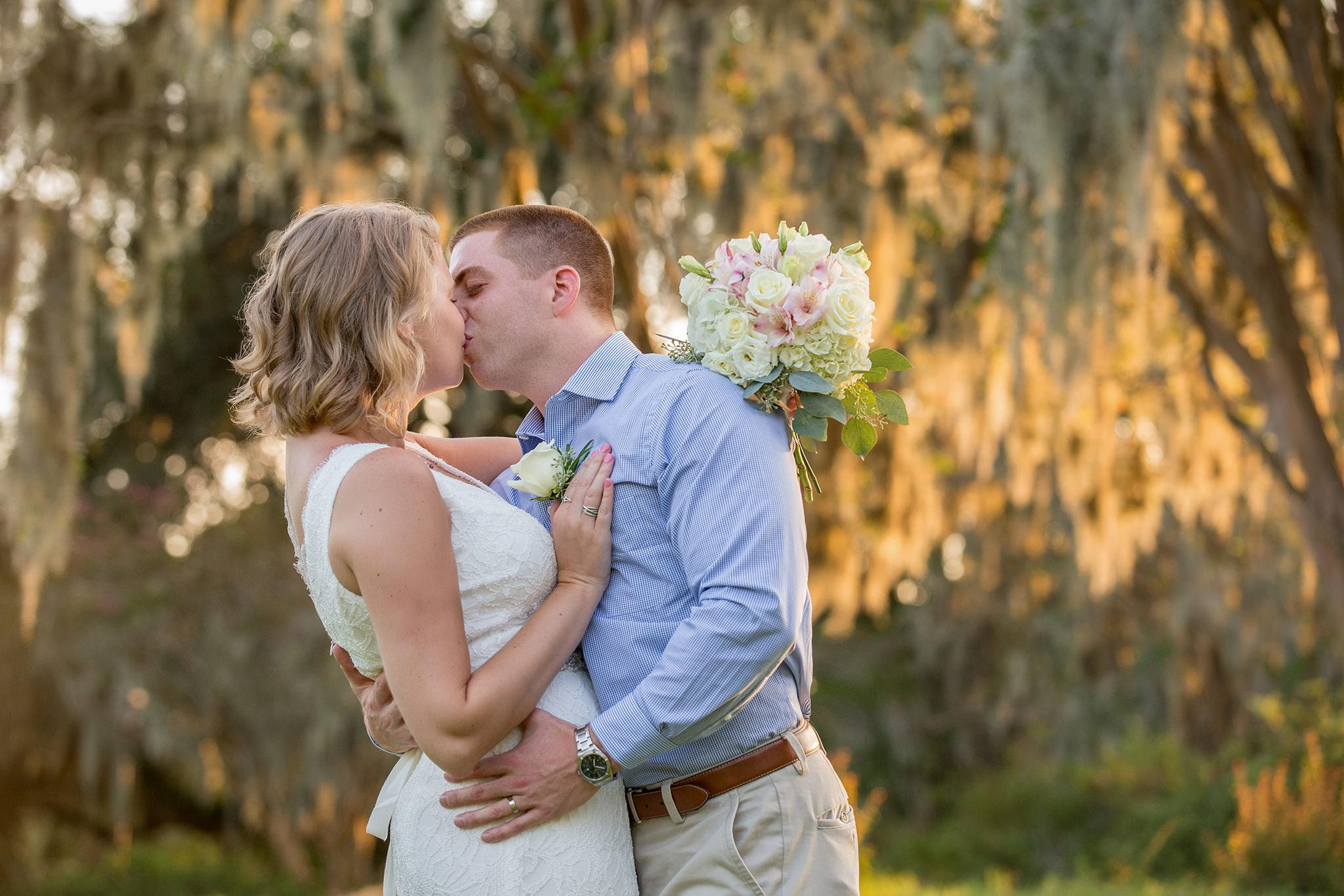 The couple is kissing, the bride holds the bouquet