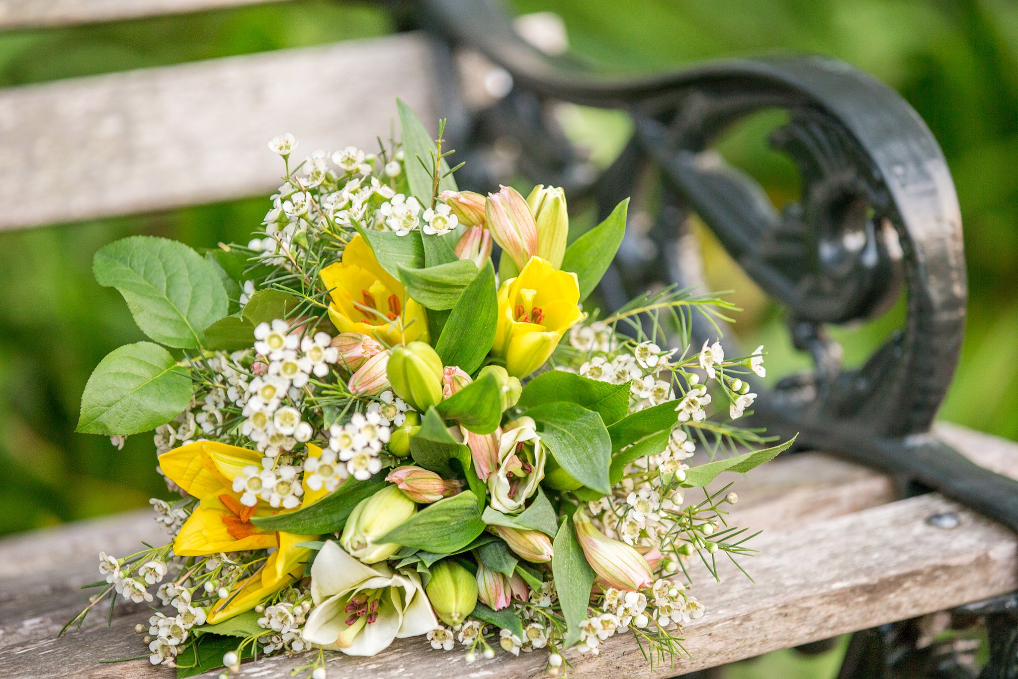 The bouquet composed of greenery, white and yellow flowers lies on the bench
