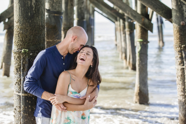 engagement photo Charleston he is hugging her while standing in the water