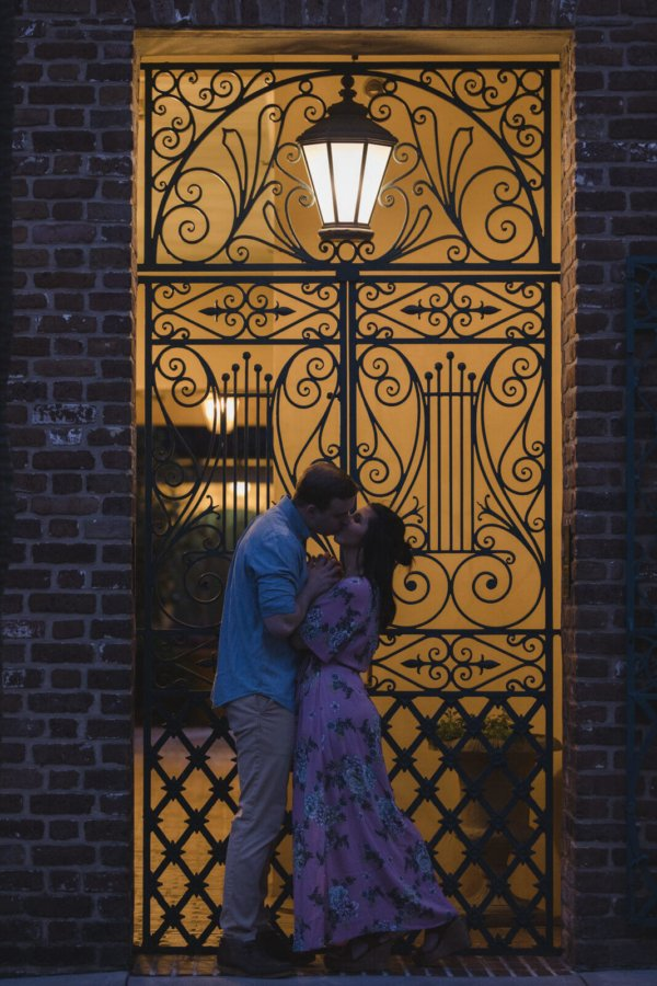 engagement photo charleston the couple is kissing under the lamp