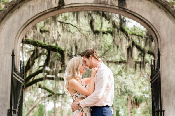 engagement photo Charleston they are hugging each other on the background of open gates