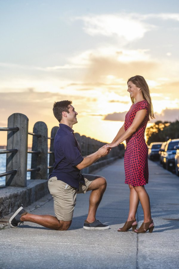 engagement photo Charleston he is proposing her on the bridge during sunset