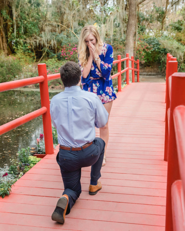 engagement photo Charleston the moment of proposal on a red bridge in Hampton Park
