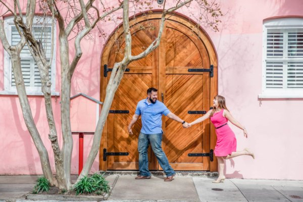 engagement photo Charleston they are running on the background of building in Downtown