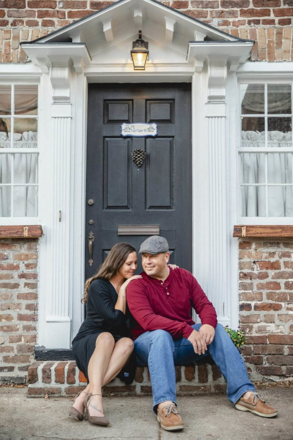 engagement photo Charleston they are sitting near door in Downtown
