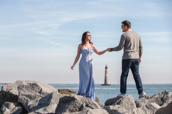 engagement photo Charleston he is holding her hand near stones