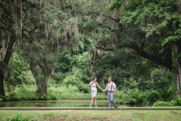 engagement photo Charleston they are walking in greenery holding their hands