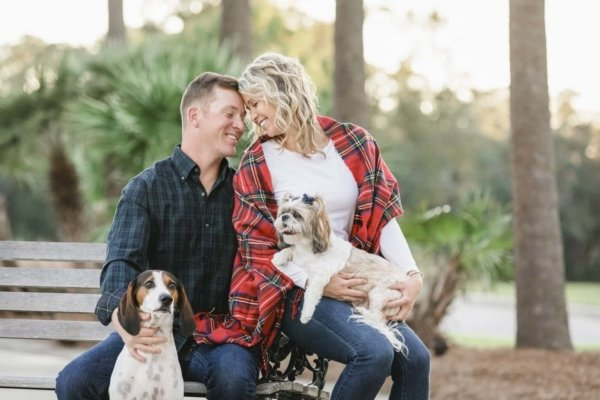 Charleston dog photo couple is holding two dogs in their hands