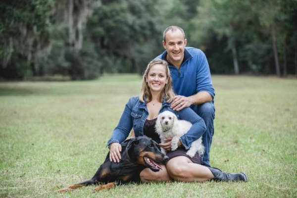 Charleston dog photo couple and their dog sitting on the grass and smiling