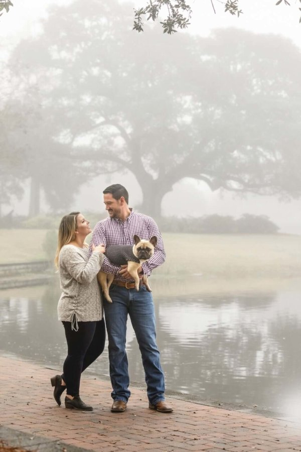 Charleston dog photo man is holding his dog he and his wife standing near lake