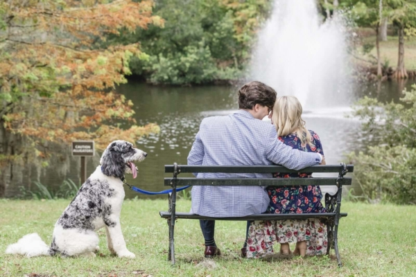 Charleston dog photo couple sitting on the bench near water and kissing while dog looking at them