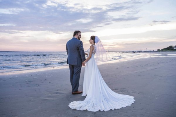Charleston wedding photo bride and groom are standing on the beach