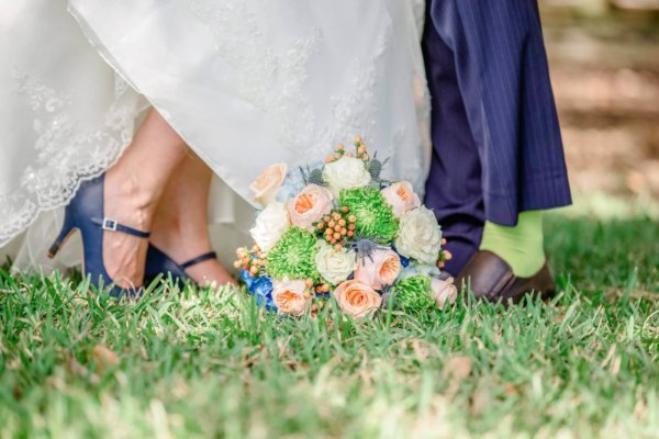 Charleston wedding photography bouquet is laying near bride and groom's legs