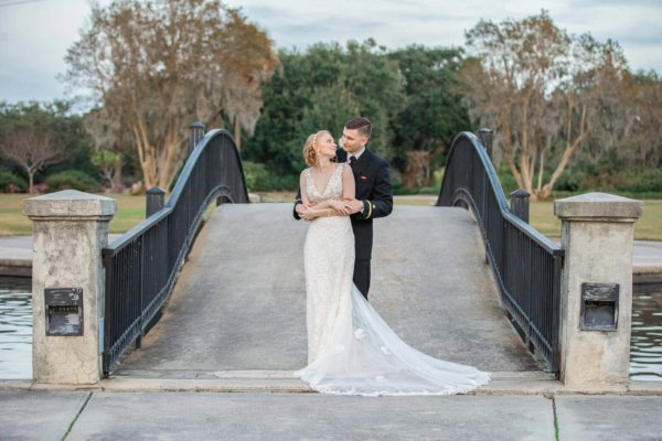 Charleston wedding photography bride and groom hugging near bridge in Hampton Park