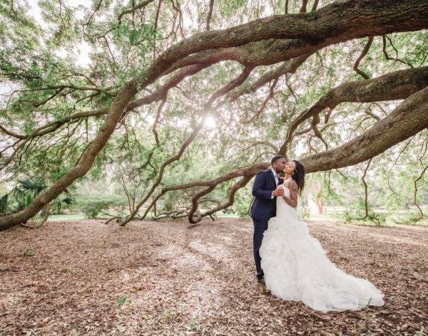 white point garden wedding photo groom and bride kissing on the background of a tree with pink flowers