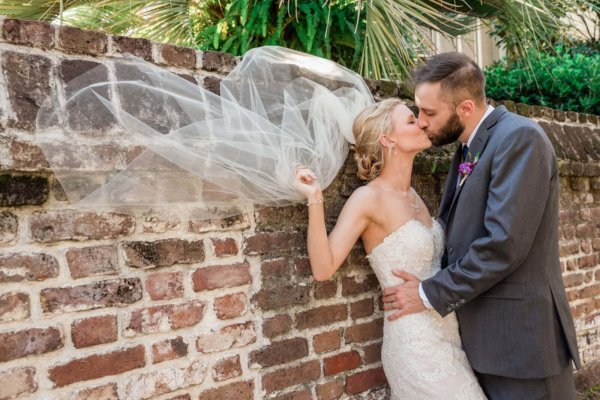 Charleston wedding photo groom is kissing bride near wall in Hampton Park