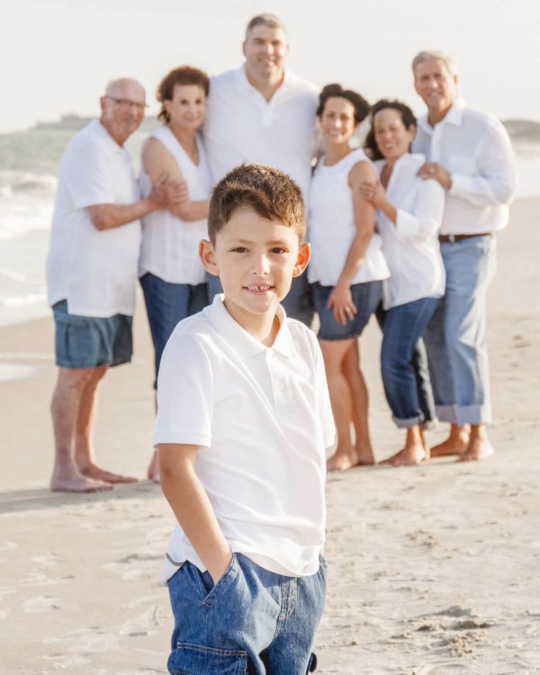 family photo Charleston boy is looking into the camera, the whole family is behind him on the beach