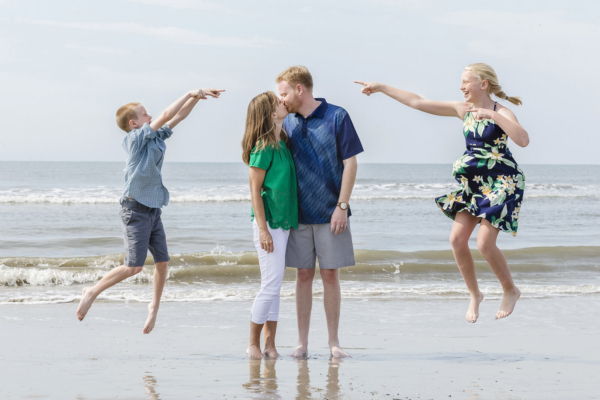 family photo charleston kids are jumping near their parents on the beach