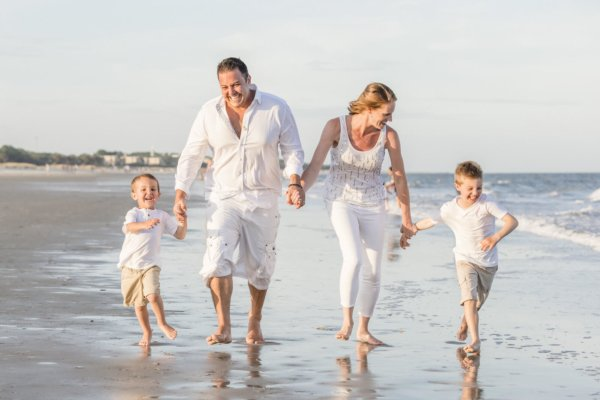 family photo charleston family is wearing white colors and walking on the beach