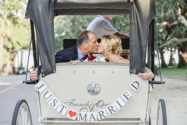 bride and groom ride in a carriage and hold the inscription just married