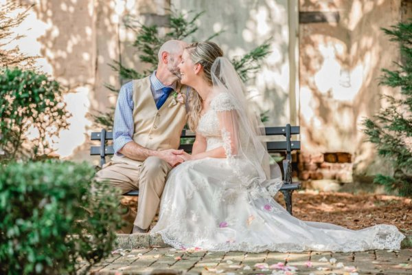 Photo wedding Charleston bride and groom are siting on the bench and kissing