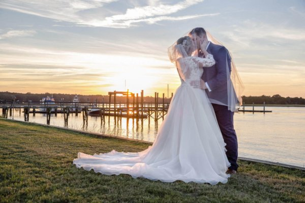 photo wedding Charleston bride and groom kissing near water during sunset